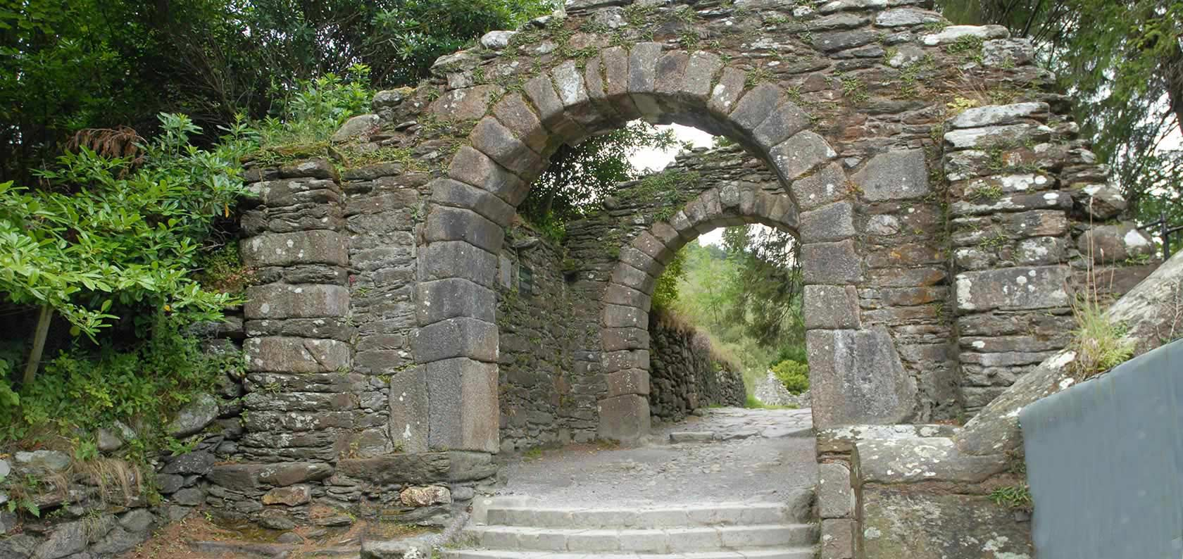 Stone archway over wooded path.